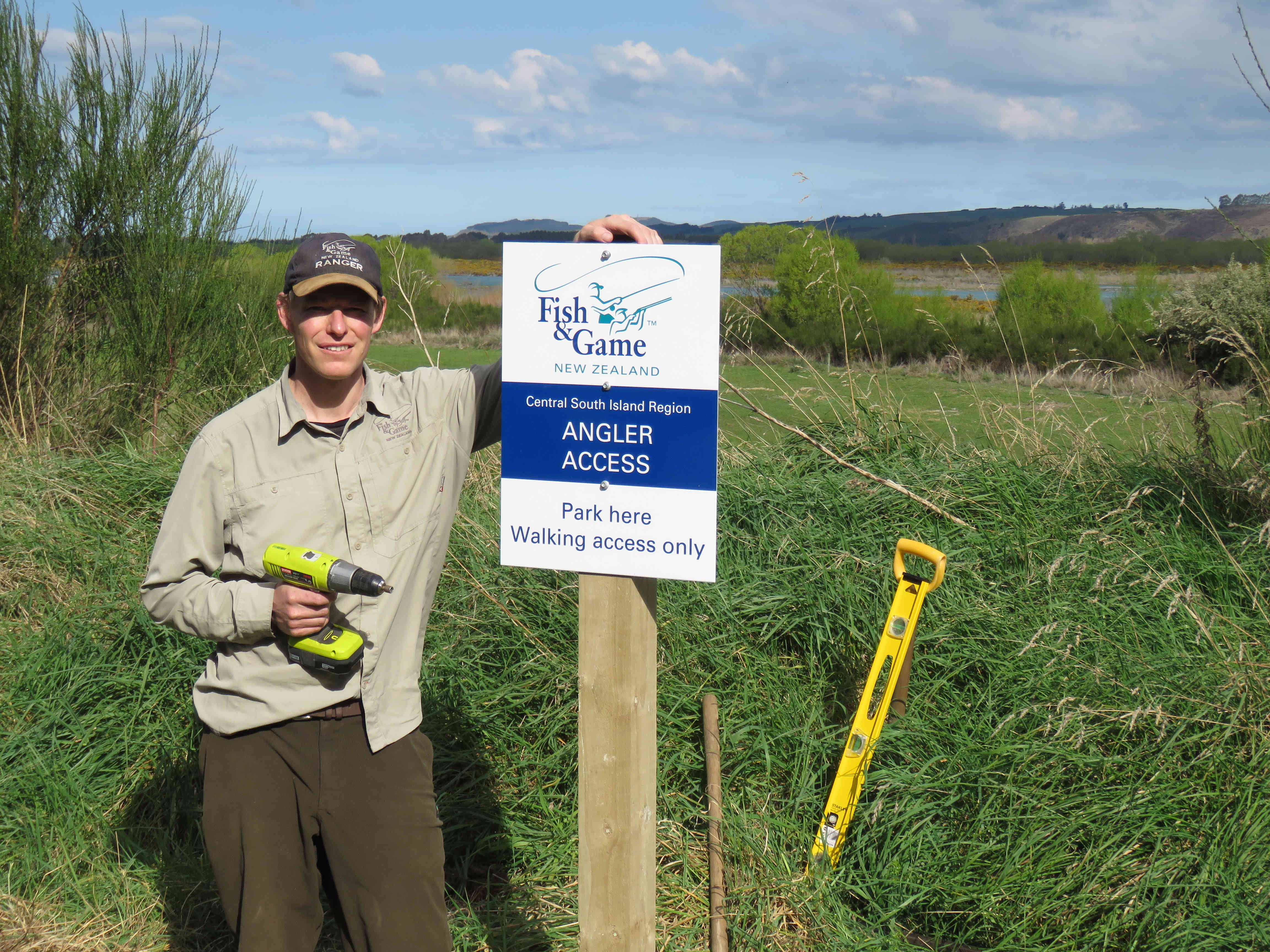 Photo 3 Fish Game Officer Rhys Adams with a newly installed angler access sign on the Waitaki River at Stone wall