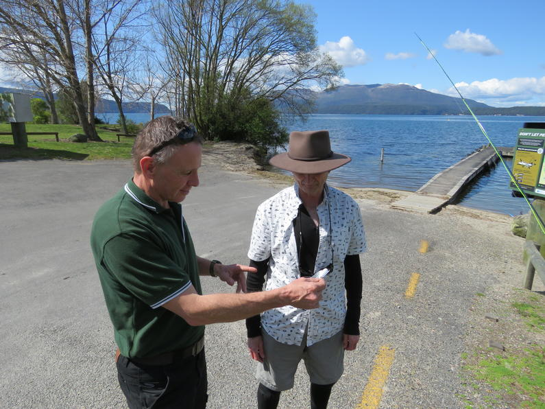 Fish Game Officer Anthony van Dorp inspects anglers licence Stony Point Lake Tarawera2.