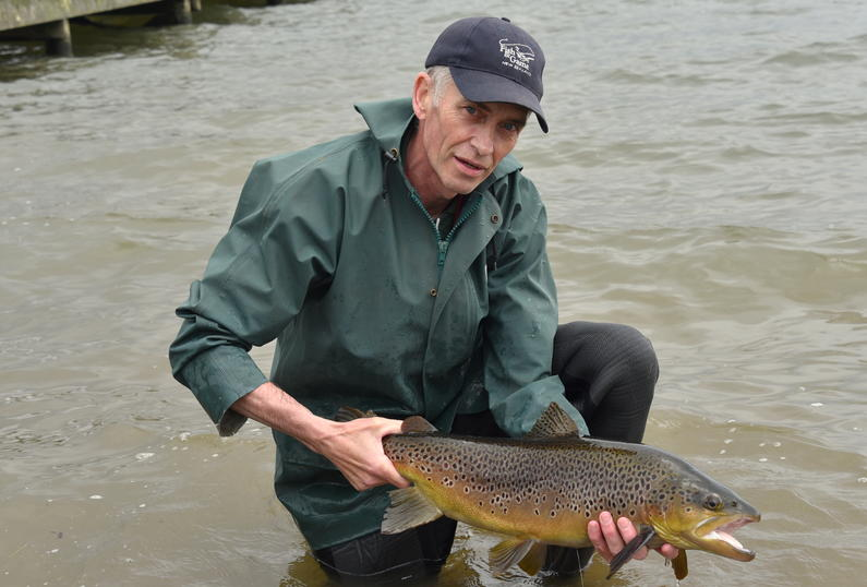 Fish Game officer Mark Sherburn frees a display pond trout in Lake Rotorua2.