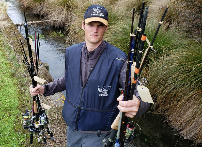 Photo 1 Fish Game Officer Hamish Stevens displays just two handfuls of the rods siezed from offending anglers over the past season 2