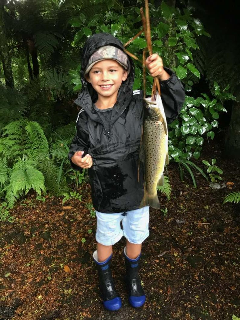 TRL1Jan18. Malakai Martin Capper proudly shows off a brown trout caught during a fresh in the lower Waiwhakiaho River photo Les Martin.